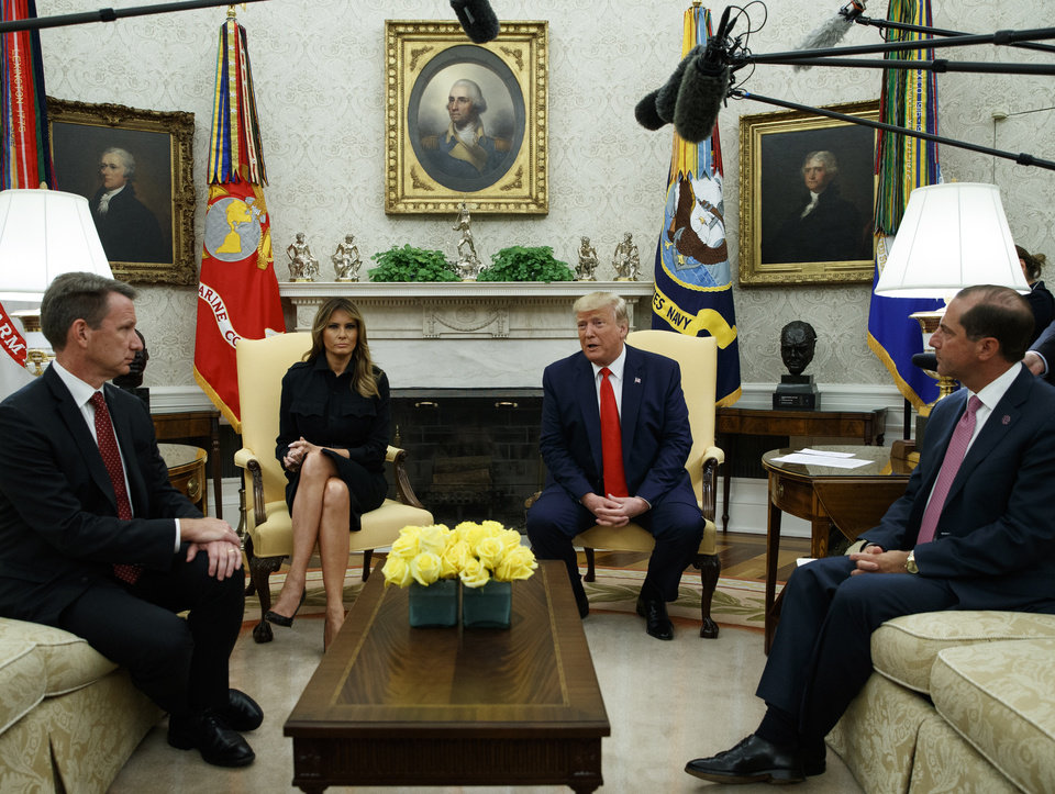 Photo -  President Donald Trump talks about a plan to ban most flavored e-cigarettes, in the Oval Office of the White House, on Wednesday in Washington. From left are acting FDA Commissioner Ned Sharpless, first lady Melania Trump, Trump, and Secretary of Health and Human Services Alex Azar. [Evan Vucci/The Associated Press]
