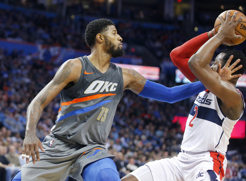Photo - Oklahoma City's Paul George (13) defends Washington's John Wall (2) during an NBA basketball game between the Oklahoma City Thunder and the Washington Wizards at Chesapeake Energy Arena in Oklahoma City, Thursday, Jan. 25, 2018. Photo by Bryan Terry, The Oklahoman