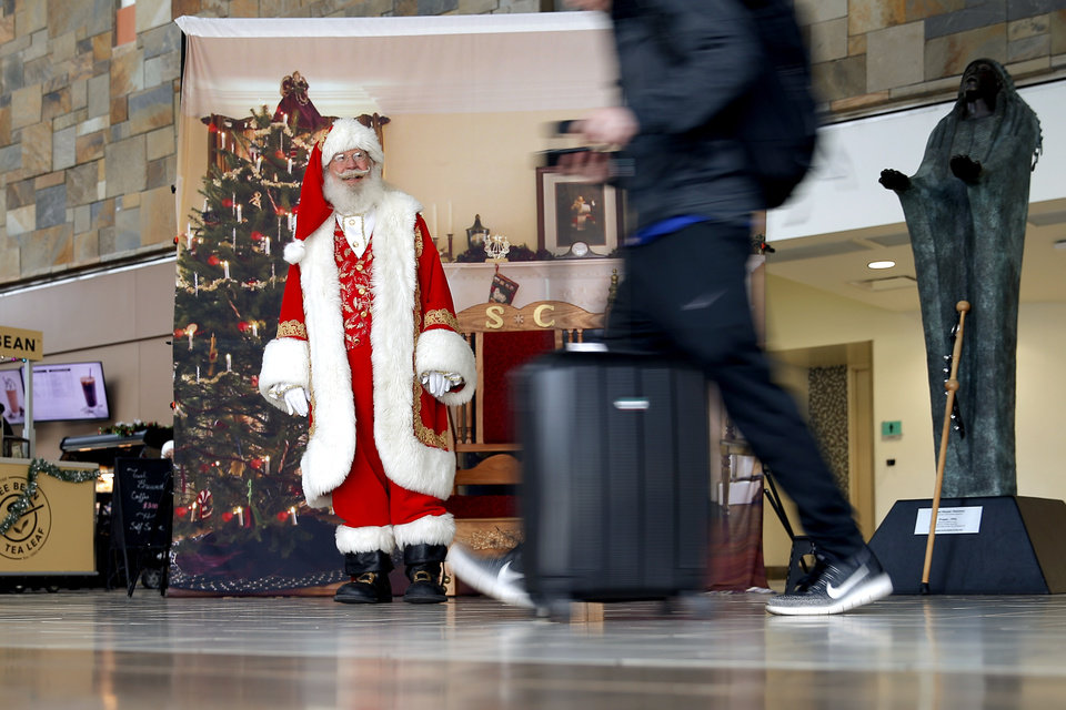 Photo -  Santa Claus greets travelers Tuesday inside Will Rogers World Airport. [Photo by Bryan Terry, The Oklahoman]