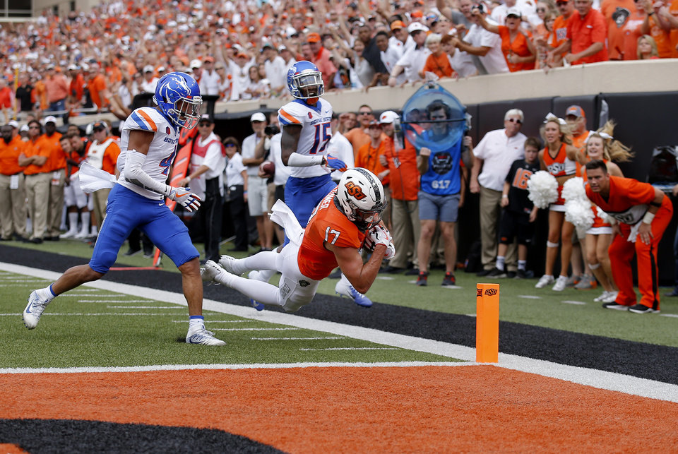 Photo - Oklahoma State's Dillon Stoner (17) dives in for a touchdown as Boise State's DeAndre Pierce (4) and Jalen Walker (15) defend in the third quarter during a college football game between the Oklahoma State Cowboys (OSU) and the Boise State Broncos at Boone Pickens Stadium in Stillwater, Okla., Saturday, Sept. 15, 2018. OSU won 44-21. Photo by Sarah Phipps, The Oklahoman