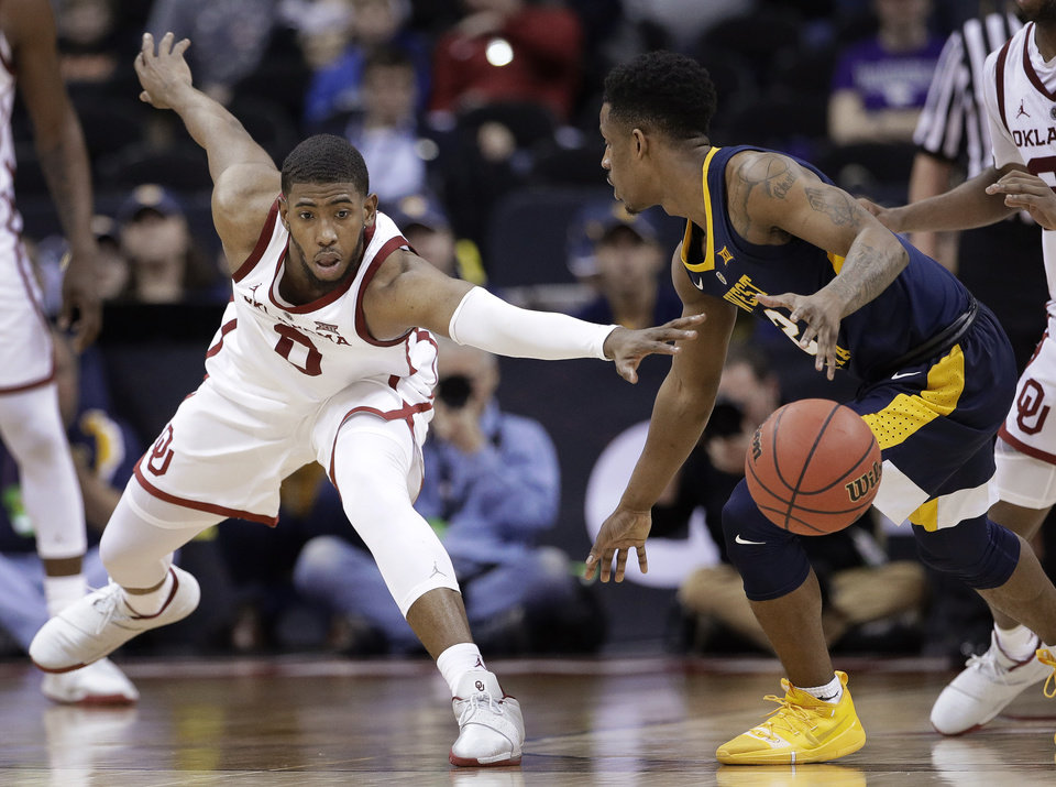 Photo - Oklahoma's Christian James (0) tries to steal the ball from West Virginia's Brandon Knapper (2) during the second half of an NCAA college basketball game in the Big 12 men's tournament Wednesday, March 13, 2019, in Kansas City, Mo. West Virginia won 72-71. (AP Photo/Charlie Riedel)