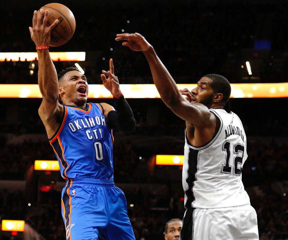 Photo - Oklahoma City's Russell Westbrook goes past San Antonio's LaMarcus Aldridge during Game 2 of the second-round series between the Oklahoma City Thunder and the San Antonio Spurs in the NBA playoffs at the AT&T Center in San Antonio, Monday, May 2, 2016. Photo by Bryan Terry, The Oklahoman