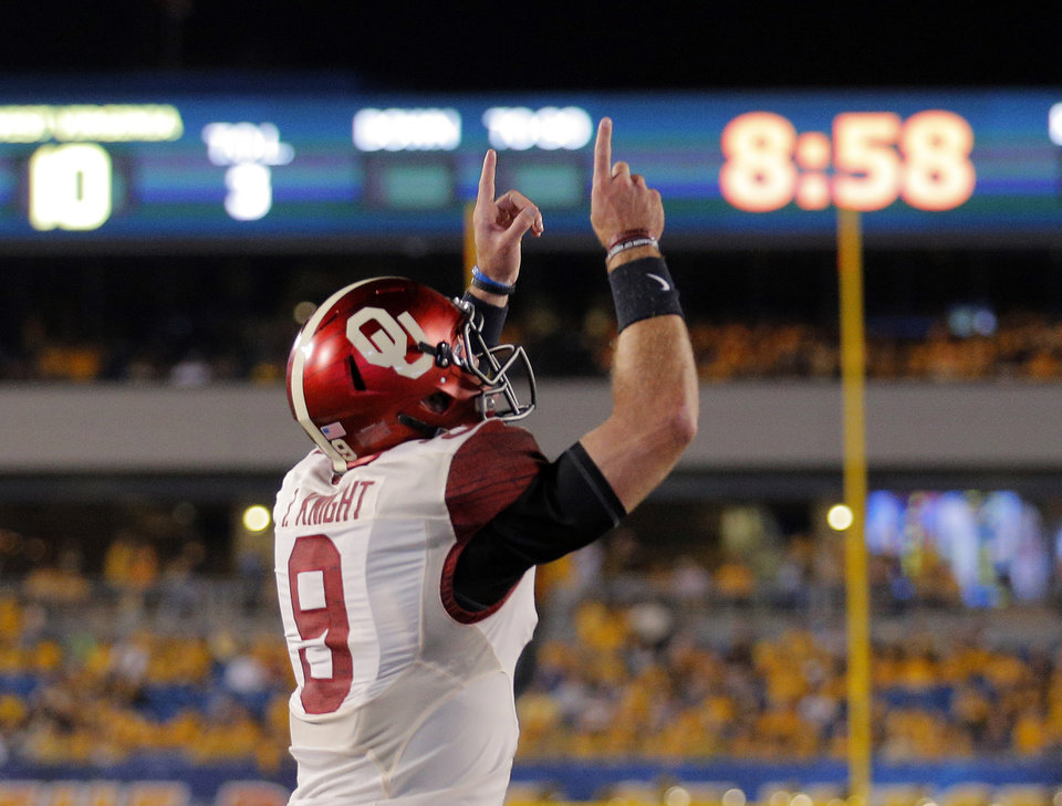 Photo - Oklahoma's Trevor Knight (9) scores a touchdown during the college football game between West Virginia  Mountaineers and the University of Oklahoma Sooners at Milan Puskar Stadium in Morgantown, W.Va., Saturday, Sept. 20, 2014. Photo by Sarah Phipps, The Oklahoman
