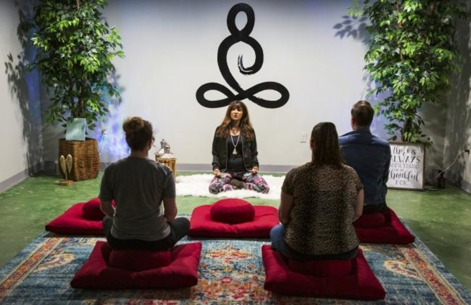 Photo -  Lauree Dash demonstrates proper meditative form Thursday in the meditation room at APCO MED, located 313 NW 23. [CHRIS LANDSBERGER/THE OKLAHOMAN]