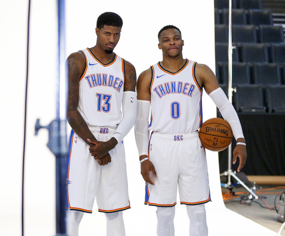 Photo - Paul George, left, and Russell Westbrook pose together during a photo shoot at media day for the Oklahoma City Thunder at Chesapeake Energy Arena in Oklahoma City, Monday, Sept. 24, 2018. Photo by Nate Billings, The Oklahoman