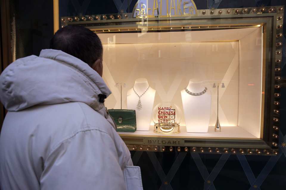 Photo -  A man looks at a Bulgari fashion shop window, in the Montenapoleone shopping district, in Milan, Italy, Tuesday, Feb. 4, 2020.  China's virus outbreak is giving global business a chill. In Milan's luxury Montenapoleone shopping district, dozens of luxury brands decked out their windows for Chinese New Year. But wealthy Chinese shoppers, who are responsible for about one-third of all luxury purchases globally, have failed to arrive in their usual numbers. (AP Photo/Luca Bruno)