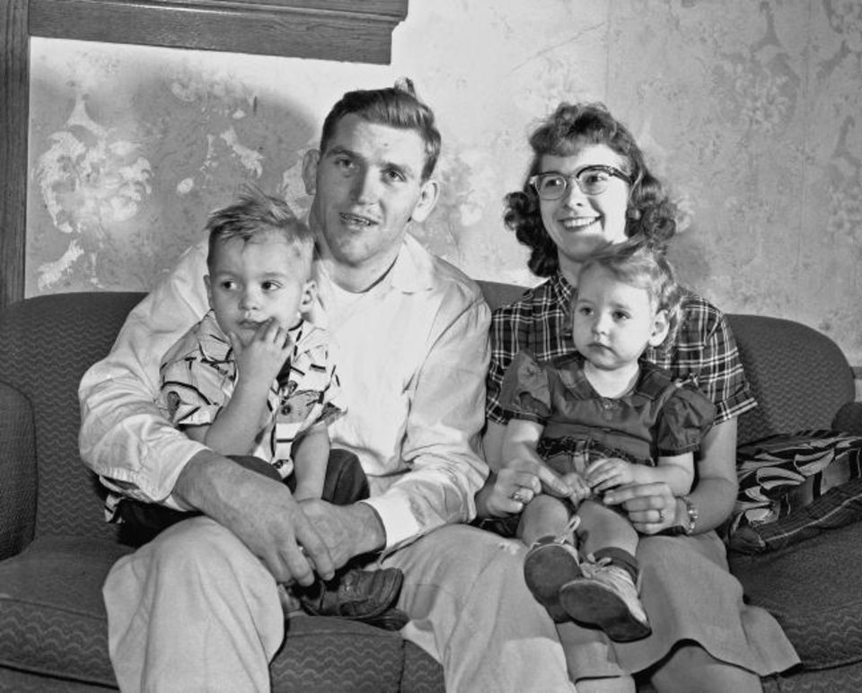 Photo -  Daniel Hodge, left, sensational OU 177-pound wrestling champ, poses with his family March 11, 1957. Shown are his wife, Dolores Hodge, right, son Daniel Allen Hodge, Jr., 3, and daughter, Linda Marie Hodge, 20 months. [AP Photo]