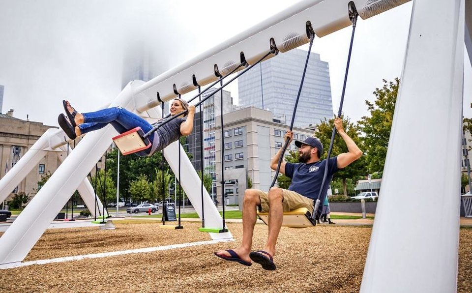 Photo - Kayla and Brandon Norman take a ride on The Musical Swings set up at Bicentennial Park in Oklahoma City, Okla. on Monday, Sept. 23, 2019. The swings are set up as part of the Oklahoma City Community Foundation's 50th anniversary.  [Chris Landsberger/The Oklahoman]