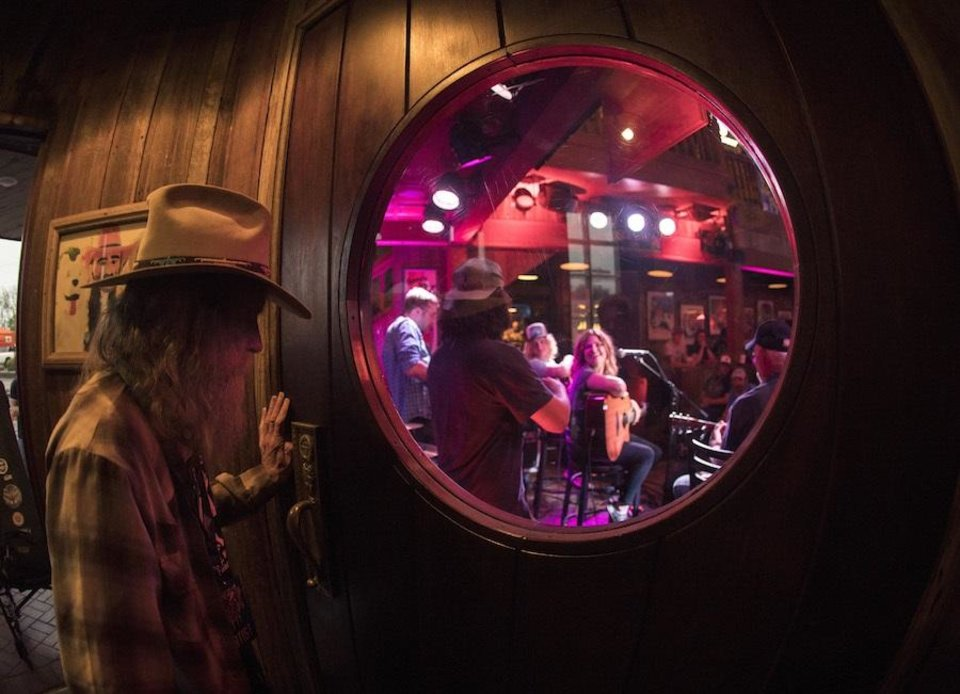 Photo - Randy Crouch watches some of his fellow songwriters perform at the 2018 Bob Childers' Gypsy Cafe songwriters festival at Eskimo Joe's in Stillwater. Crouch will recieve the Restless Spirit Award at this year's festival [Photo by Nathan Poppe]