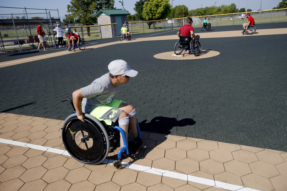 Photo -  Zion Redington, 11, races to first base during the wheelchair softball competition at the Endeavor Games at Mitch Park in Edmond on Sunday. [PHOTO BY SARAH PHIPPS, THE OKLAHOMAN]