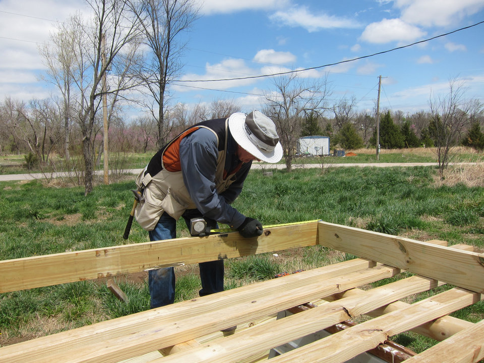 Photo - Bill Downes, of Council Groves, Kan., builds a front deck at a Newalla home as part of a NOMADS project in the Oklahoma City metro area.  Photo by Carla Hinton, The Oklahoman