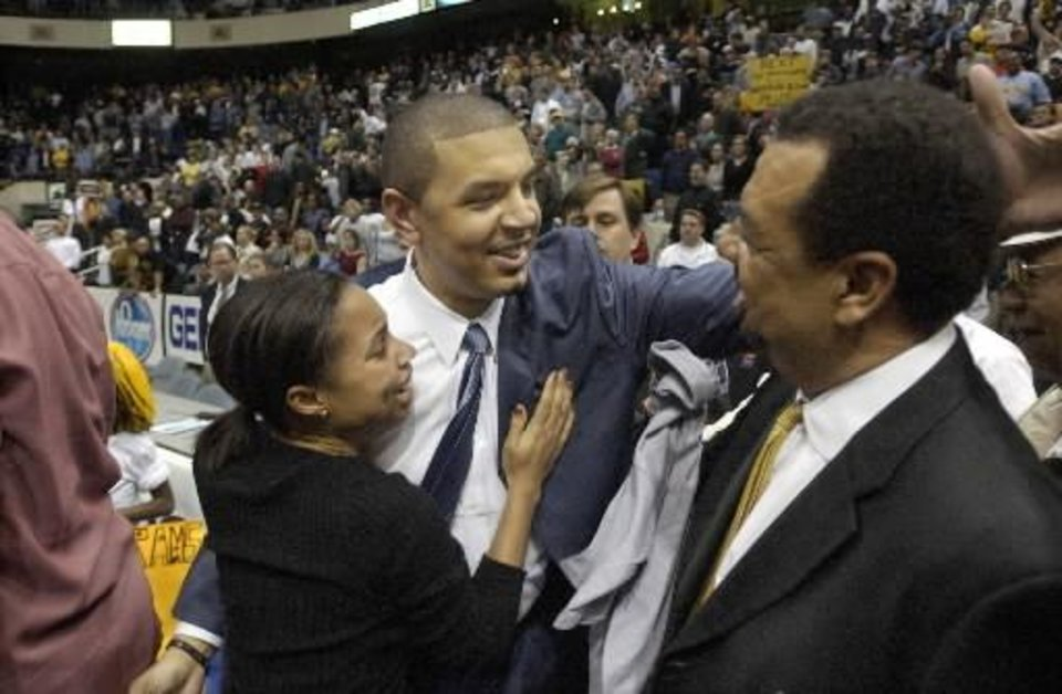 Photo - VCU coach Jeff Capel is hugged by wife Kanika (left) and father Jeff (right) as he celebrates his team's win over George Mason in the Colonial Athletic Association championship game at the Coliseum in Richmond, Va. on Mon., March 8, 2004. Capel, who is the youngest coach in men's Div. I basketball, will make his first trip to the NCAA tournament in only his second season as a coach. Photos provided to The Oklahoman by the Richmond Times-Dispatch
