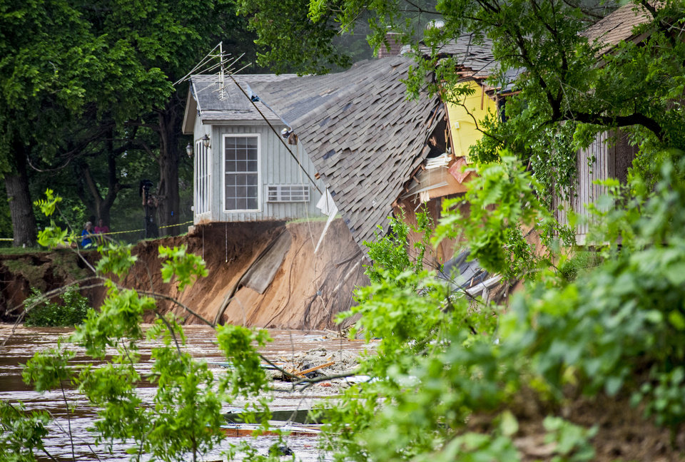 Photo - An abandoned home is washed away by the flood waters rushing down the river in the Twin Lakes community near Cimarron City, Okla. on Wednesday, May 22, 2019.  [Chris Landsberger/The Oklahoman]