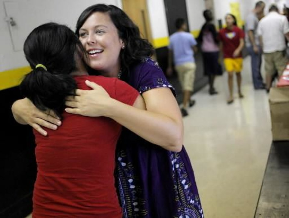 Photo - Teacher Marcie Levy gets a hug from former student Estfany De La Fuente (CQ) ESTFANY, who graduated in 2010, during the Back 2 School Bash at Santa Fe South Charter High School in Oklahoma City on Monday, Aug. 1, 2011. De La Fuente was at the school helping her cousin, who is a freshman this year. Photo by John Clanton