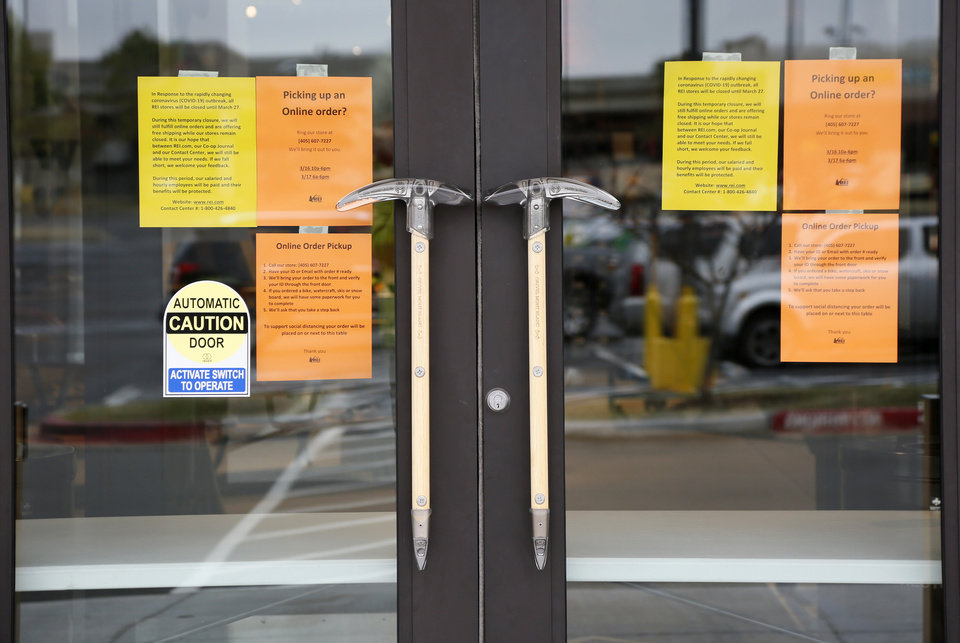Photo - Signs on the door of the REI Co-op in Oklahoma City give information about the store's temporary closure, Monday, March 16, 2020. REI has closed all of its retail stores until March 27 because of the coronavirus pandemic. [Nate Billings/The Oklahoman]