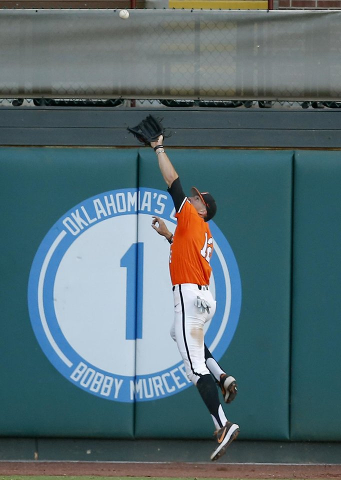 Photo - Oklahoma State's Carson McCusker (12) makes a catch in the 4th inning during the Oklahoma City Regional NCAA baseball game between Oklahoma State University (OSU) and UConn at Chickasaw Bricktown Ballpark in Oklahoma City,  Monday, June 3, 2019. [Sarah Phipps/The Oklahoman]