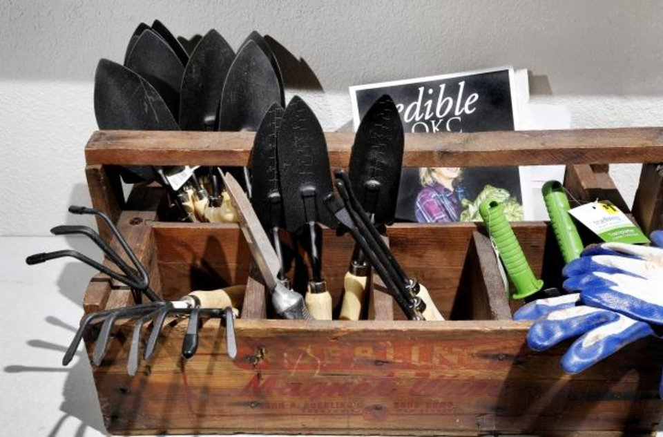 Photo -  A variety of gardening tools and gloves sit in a wooden tool box at Restore OKC in northeast Oklahoma City. [Jim Beckel/The Oklahoman]