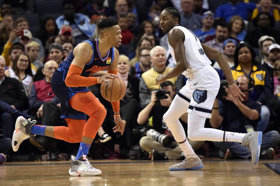 Photo - Oklahoma City Thunder guard Russell Westbrook, left, is defended by Memphis Grizzlies forward Justin Holiday during the first half of an NBA basketball game Monday, March 25, 2019, in Memphis, Tenn. (AP Photo/Brandon Dill)