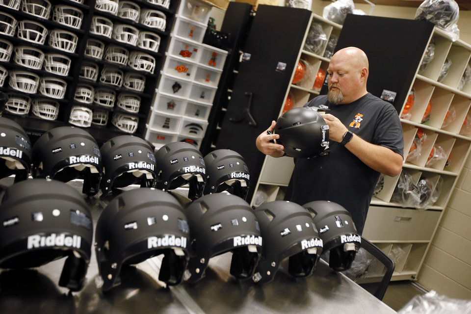 Photo -  Len Magby, OSU assistant director of football equipment, prepares new game helmets for players at Boone Pickens Stadium in Stillwater. [PHOTO BY NATE BILLINGS, THE OKLAHOMAN]