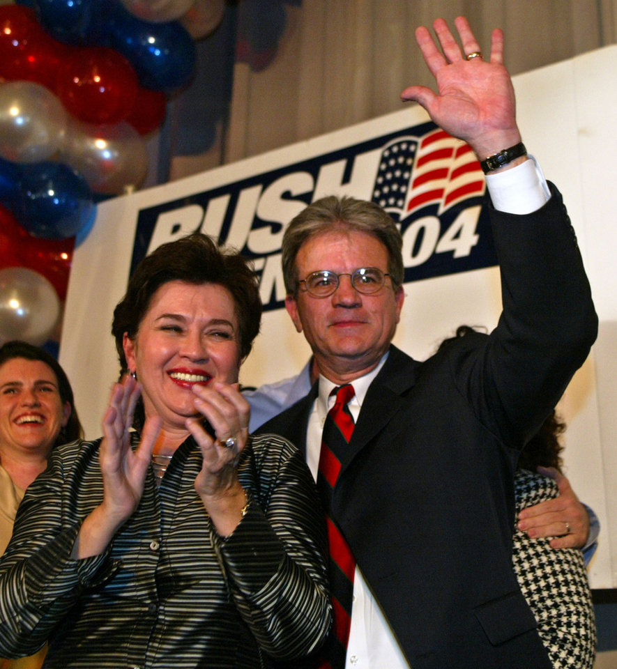 Photo - Dr. Tom Coburn, Republican candidate for the U.S. Senate from Oklahoma, waves to the crowd as his wife, Carolyn, left, applauds, following his victory speech in Oklahoma City, Tuesday, Nov. 2, 204. (AP Photo/Sue Ogrocki)