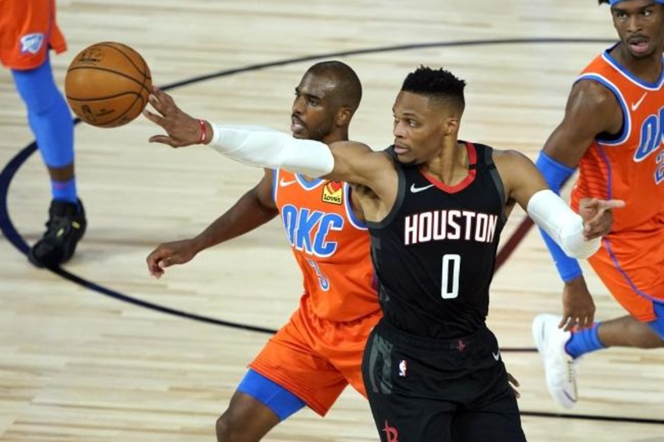 Photo -  Houston Rockets' Russell Westbrook tips the ball past Oklahoma City Thunder's Chris Paul (3) during the second half of an NBA basketball first round playoff game Saturday, Aug. 29, 2020, in Lake Buena Vista, Fla. (AP Photo/Ashley Landis)
