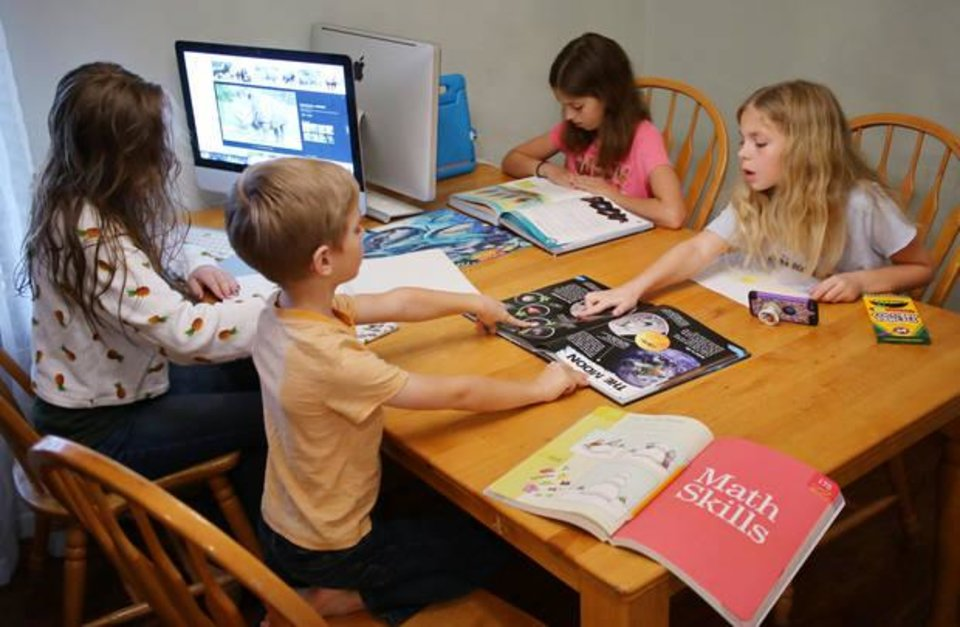 Photo -  The Chandler children work on their home school assignments at the table in their Edmond home. From left are, Denae, 15, Zak, 6, Naomi, 12 and Aliya, 10. [Photo by Doug Hoke, The Oklahoman]
