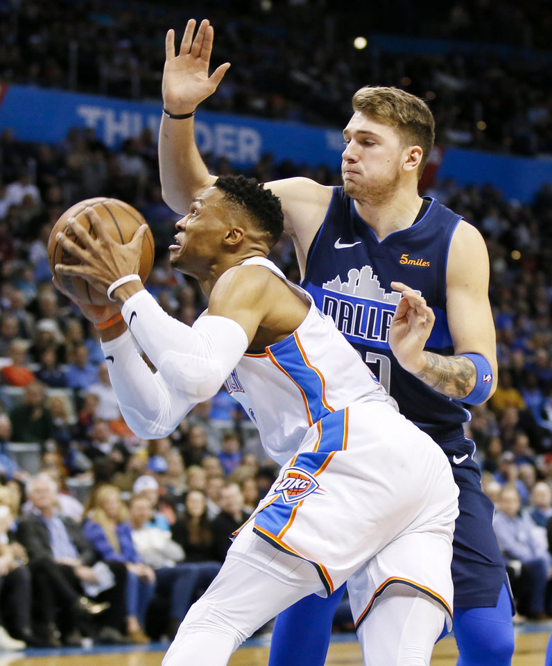 Photo - Oklahoma City's Russell Westbrook (0) takes the ball past Dallas' Luka Doncic (77) during an NBA basketball game between the Oklahoma City Thunder and Dallas Mavericks at Chesapeake Energy Arena in Oklahoma City, Monday, Dec. 31, 2018. Photo by Nate Billings, The Oklahoman