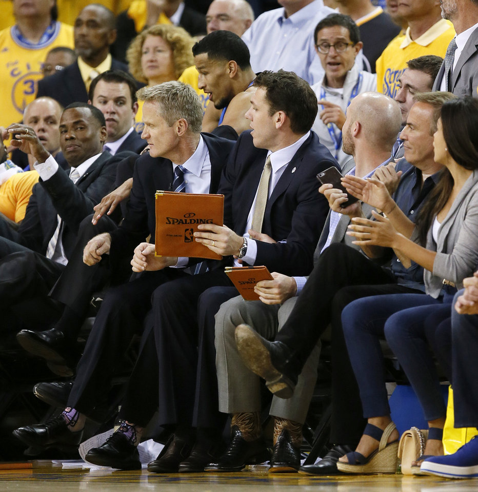 Photo - Oklahoma City's Andre Roberson (21) lands next to Warriors coach Steve Kerr, second from left, after flying into the Golden State bench during Game 5 of the Western Conference finals in the NBA playoffs between the Oklahoma City Thunder and the Golden State Warriors at Oracle Arena in Oakland, Calif., Thursday, May 26, 2016. The Warriors won 120-111. Photo by Nate Billings, The Oklahoman