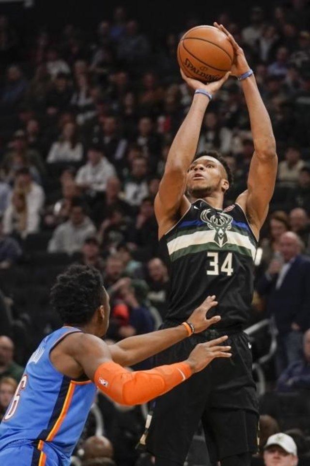 Photo -  Milwaukee's Giannis Antetokounmpo shoots over Oklahoma City's Hamidou Diallo during the second half Friday. [AP Photo/Morry Gash]