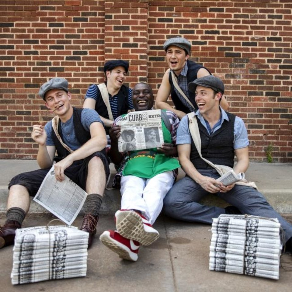 Photo -  Curbside Chronicle vendor Robert poses for a photo with cast members of Newsies in the Plaza District. [Nathan Poppe/The Curbside Chronicle]