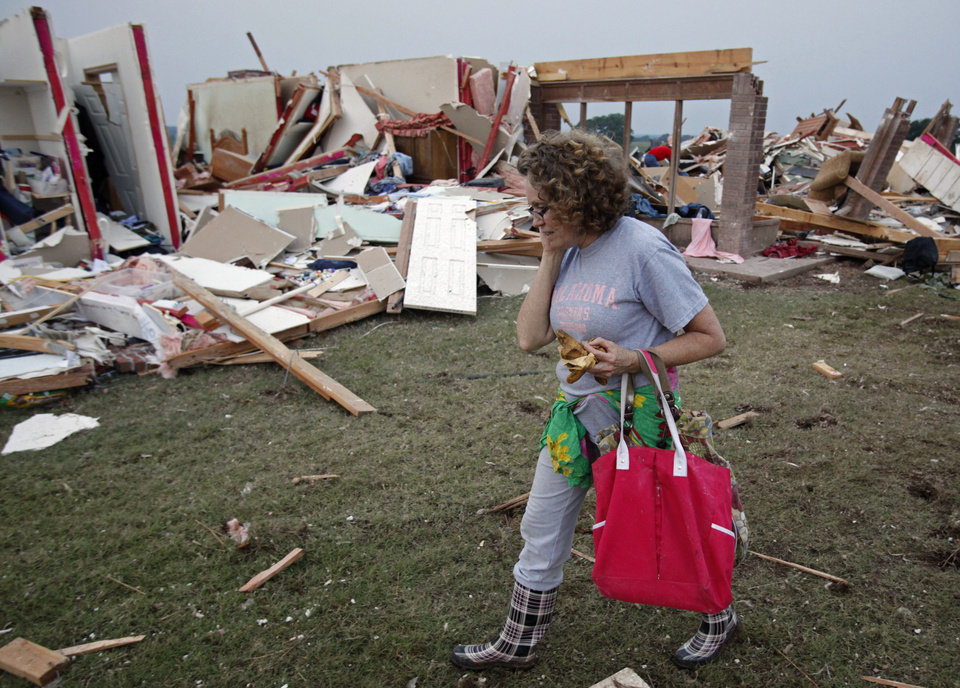 Photo - Ann Smith talks with friends in front of what is left of her house after a tornado-spawning storm swept through the state on Tuesday, May 24, 2011, in Washington, Okla.  She and her husband were in an outside storm shelter when the storm destroyed their rural home. Photo by Steve Sisney, The Oklahoman