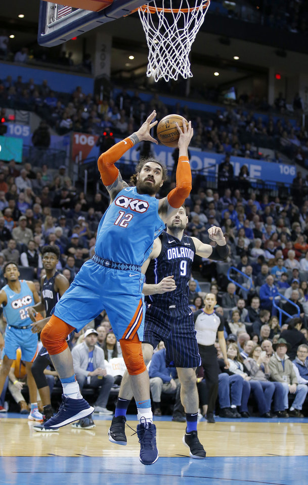 Photo - Oklahoma City's Steven Adams (12) goes up for a basket in front of Orlando's Nikola Vucevic (9) during the NBA game between the Oklahoma City Thunder and the Orlando Magic at the Chesapeake Energy Arena  Tuesday, Feb. 5, 2019. Photo by Sarah Phipps, The Oklahoman