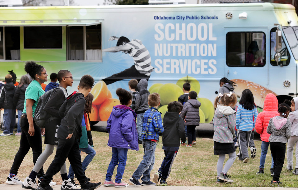 Photo - Students walk outside to receive sack lunches from a food truck provided by Oklahoma City Public Schools Nutrition Services on Monday, April 2, 2018. As a result of the teacher walkout, children who spent their day at the Boys and Girls Club of Oklahoma County  received free lunches from the school district. Photo by Jim Beckel, The Oklahoman