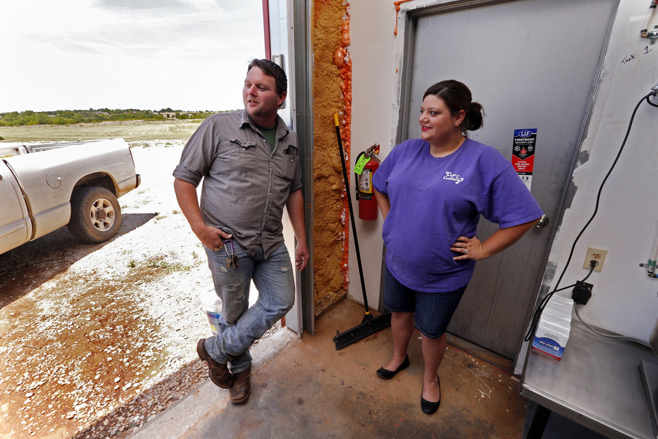 Photo -  Ricky Sowers and wife, Georgia, talk Wednesday about their Okie Shine distillery in Tuttle. He produces the moonshine, and she bottles and labels the product, while also developing ideas for drinks using their moonshine. [Photo by Steve Sisney, The Oklahoman]