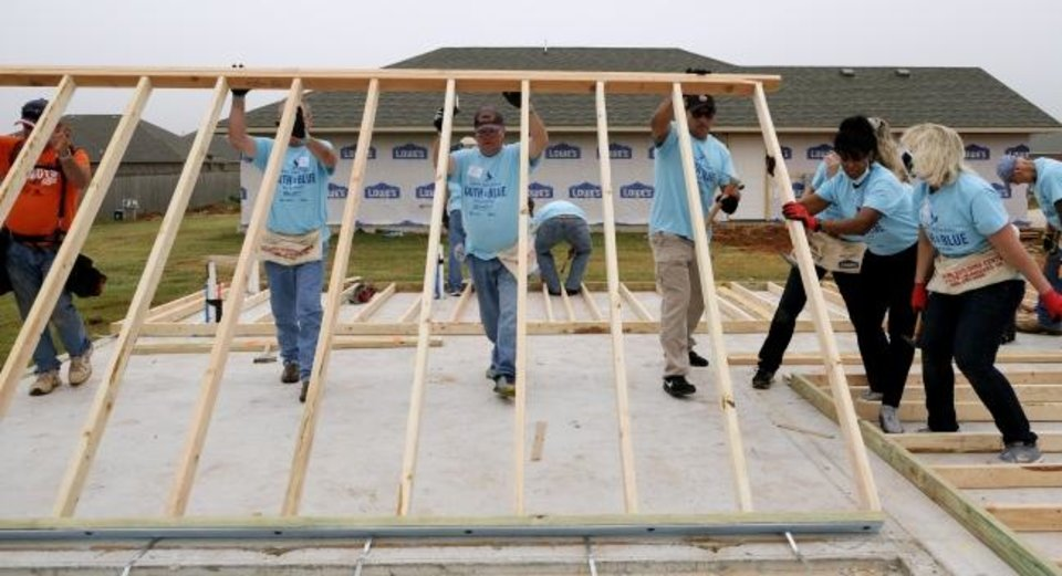 Photo -  Lifting the first wall, Oklahoma City Police Department officers and employees work with church members to building a Habitat for Humanity home together on Friday as part of the