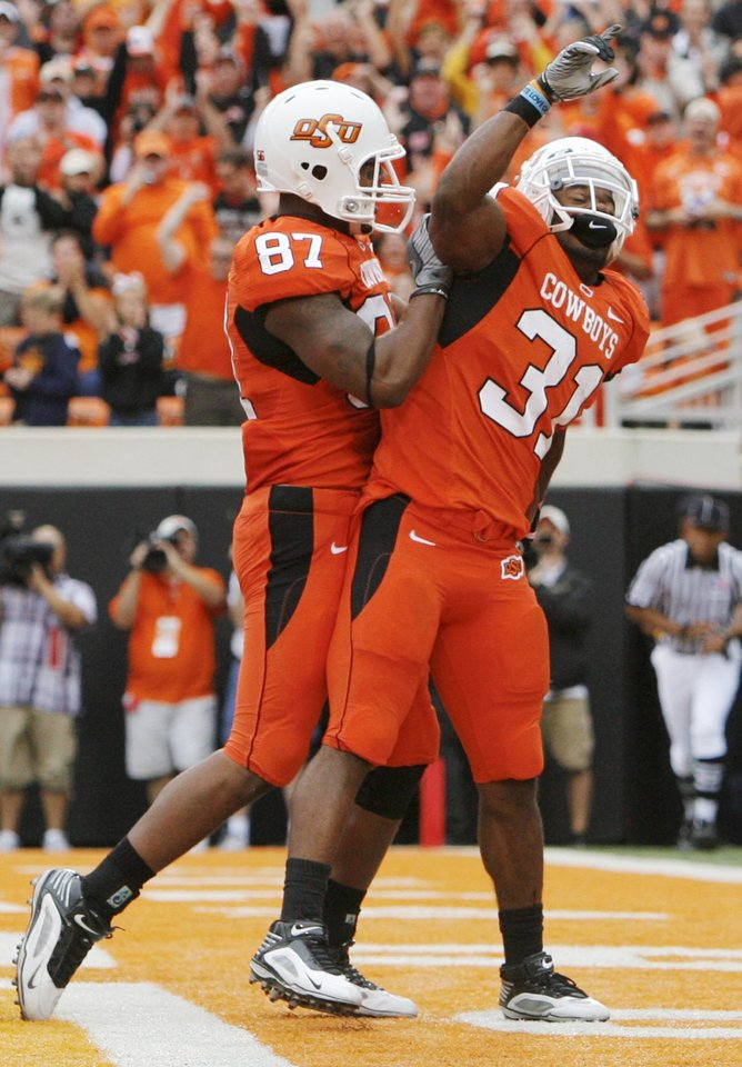 Photo - OSU's Tracy Moore (87) and Jeremy Smith (31) celebrate a touchdown by Smith in the first quarter during the college football game between the Oklahoma State Cowboys (OSU) and the Nebraska Huskers (NU) at Boone Pickens Stadium in Stillwater, Okla., Saturday, Oct. 23, 2010. Photo by Nate Billings, The Oklahoman