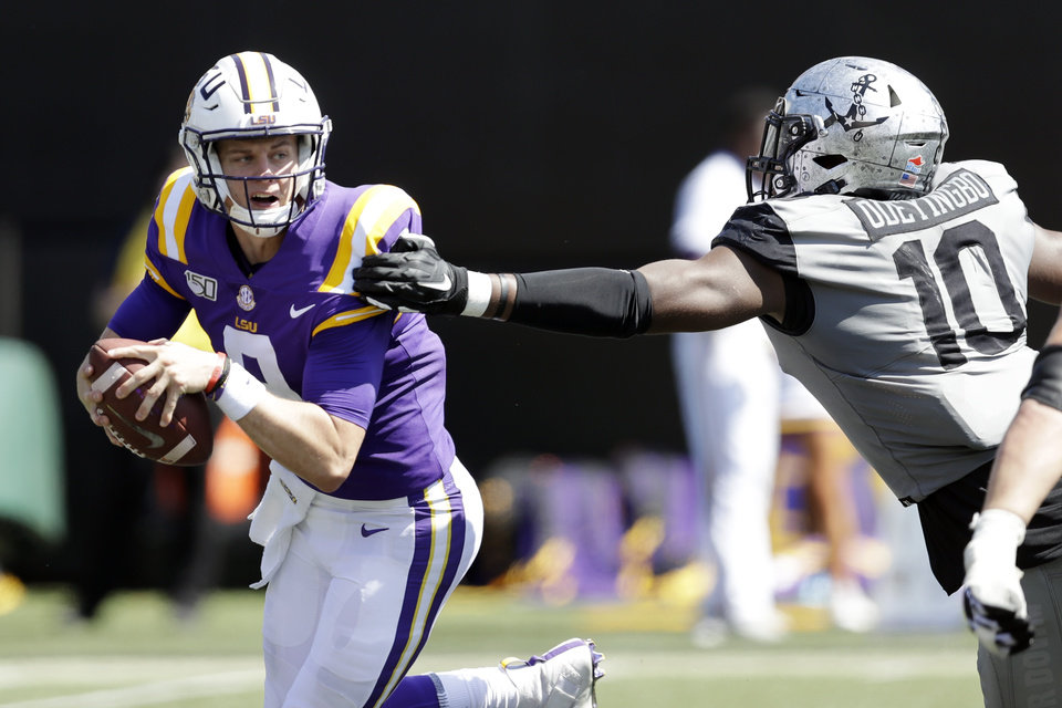 Photo - LSU quarterback Joe Burrow, left, scrambles away from Vanderbilt defensive lineman Dayo Odeyingbo (10) in the first half of an NCAA college football game Saturday, Sept. 21, 2019, in Nashville, Tenn. (AP Photo/Mark Humphrey)