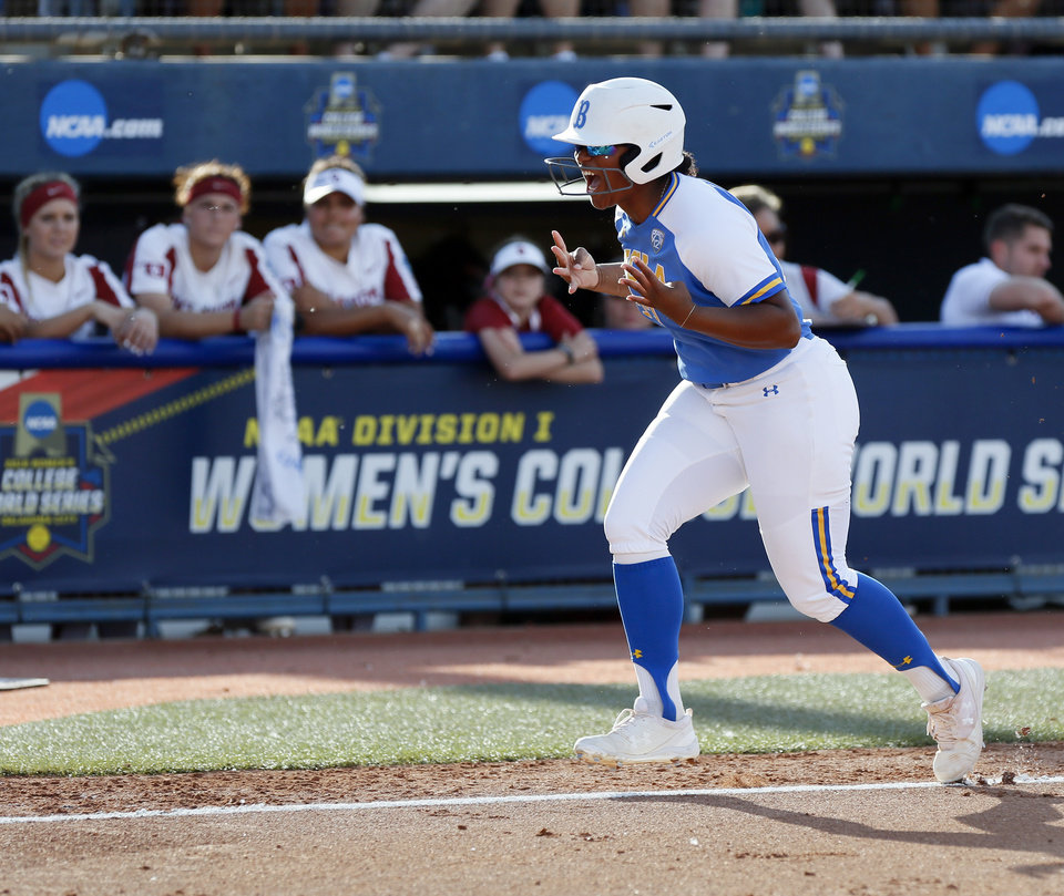 Photo - UCLA's Aaliyah Jordan (23) runs home past the OU dugout after hitting a home run in the first inning during the first NCAA softball game in the  championship series of the Women's College World Series between Oklahoma and UCLA at USA Softball Hall of Fame Stadium in Oklahoma City, Monday, June 3, 2019. [Nate Billings/The Oklahoman]