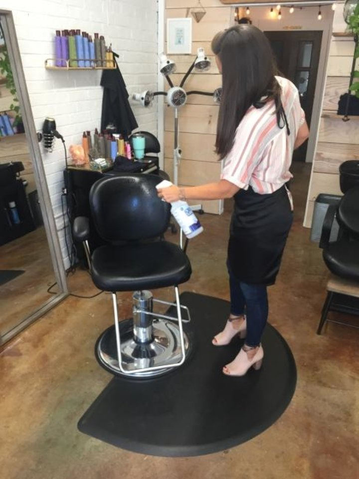 Photo -  Sarah Patton, co-owner of Twelve 06 Salon in downtown Edmond, disinfects her stylist chair at the end of her workday. [PAULA BURKES/THE OKLAHOMAN]