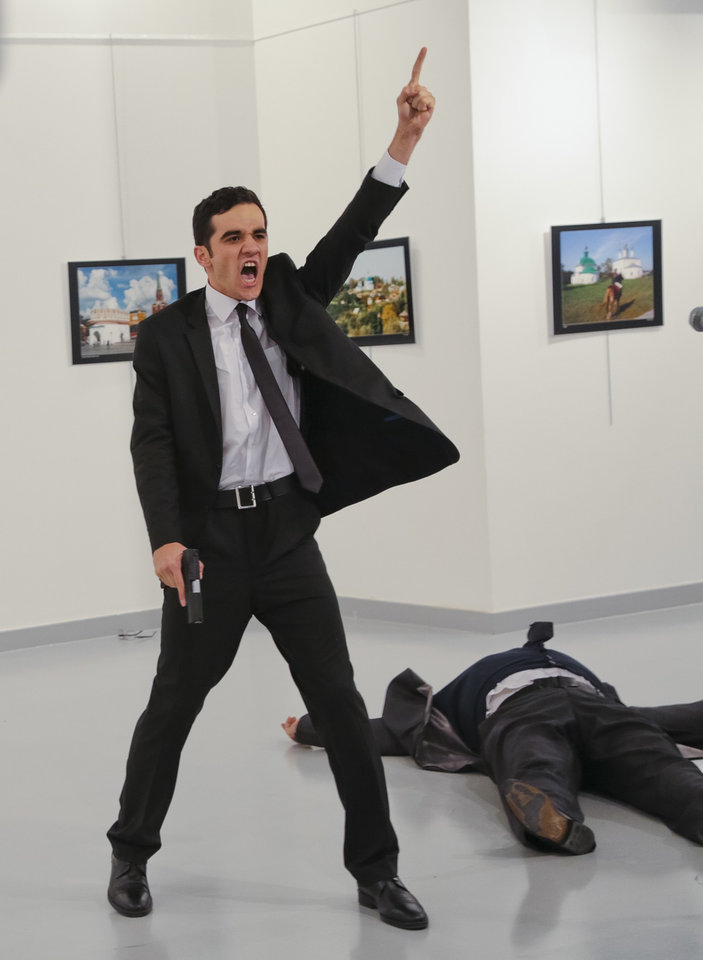 Photo - A gunman gestures after shooting the Russian ambassador to Turkey, Andrei Karlov, at a photo gallery Monday in Ankara. The Russian ambassador died later Monday. [AP Photo/Burhan Ozbilici]