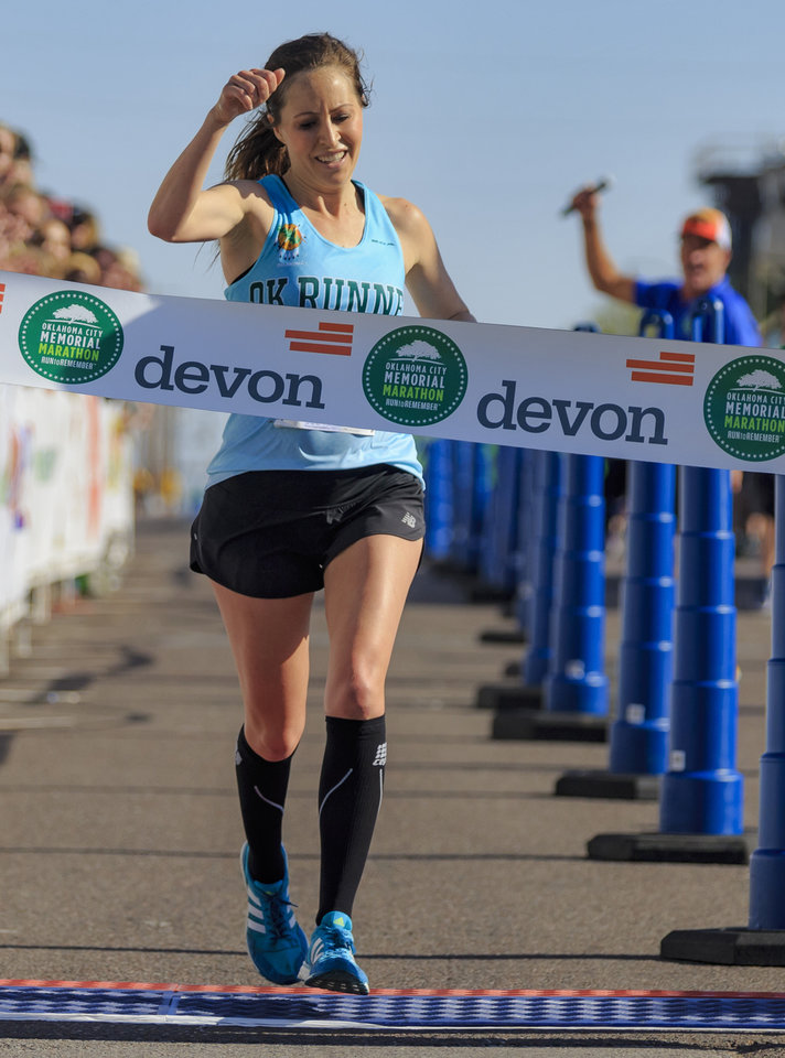 Photo -  Kristen Radcliff of Oklahoma City crosses the finish line to win the women's portion of the Oklahoma City Memorial Marathon on Sunday. [PHOTO BY CHRIS LANDSBERGER, THE OKLAHOMAN]