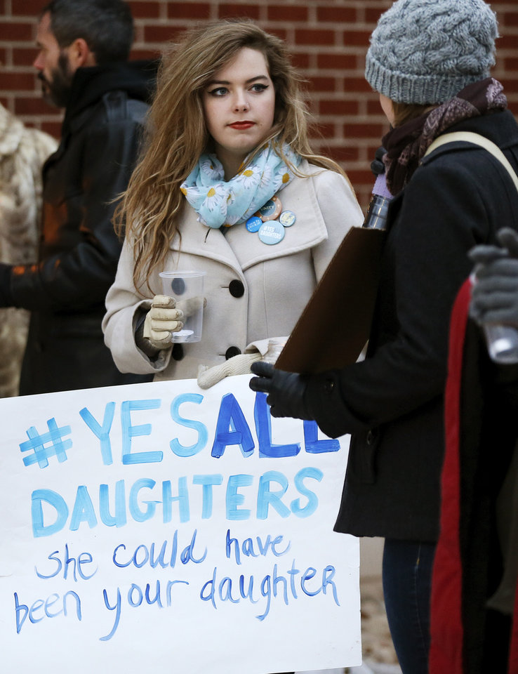 Photo - Norman High School sophomore Jessica Riley, 15, left, holds a sign as she talks to OU student Kelsey Higley, of Tulsa during a candlelight vigil outside the Board of Education meeting for Norman Public Schools at 131 S. Flood in Norman, Okla., Monday, Dec. 1, 2014. The vigil was in response to sexual assaults and bullying at Norman High School. Photo by Nate Billings, The Oklahoman