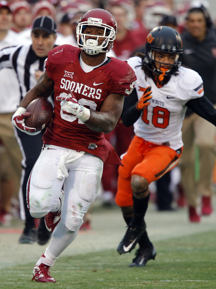 Photo - Oklahoma's Samaje Perine (32) runs down the sideline past Oklahoma State's Ramon Richards (18) during a Bedlam college football game between the University of Oklahoma Sooners (OU) and the Oklahoma State University Cowboys (OSU) at the Gaylord Family Oklahoma Memorial Stadium in Norman, Okla. on Saturday, Dec. 6, 2014. Photo by Chris Landsberger, The Oklahoman