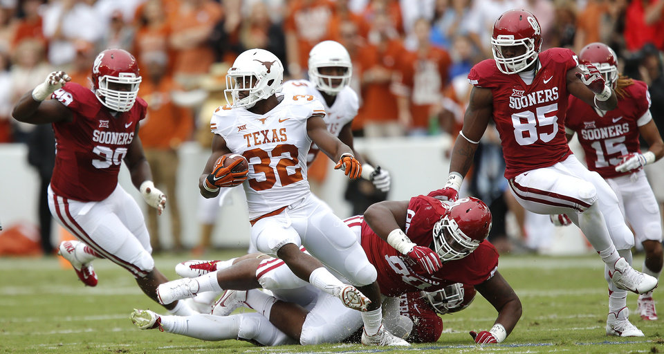 Photo - Texas' Johnathan Gray (32) tries to turn away from the Oklahoma defense during the college football game between the University of Oklahoma Sooners (OU) and the University of Texas Longhorns (UT) during the Red River Showdown at the Cotton bowl in Dallas, Texas on Saturday, Oct. 11, 2014. Photo by Chris Landsberger, The Oklahoman