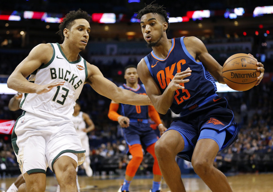 Photo - Oklahoma City's Terrance Ferguson (23) handles the ball against Milwaukee's Malcolm Brogdon (13) during an NBA basketball game between the Milwaukee Bucks and the Oklahoma City Thunder at Chesapeake Energy Arena in Oklahoma City, Sunday, Jan. 27, 2019. Oklahoma City won 118-112. Photo by Nate Billings, The Oklahoman