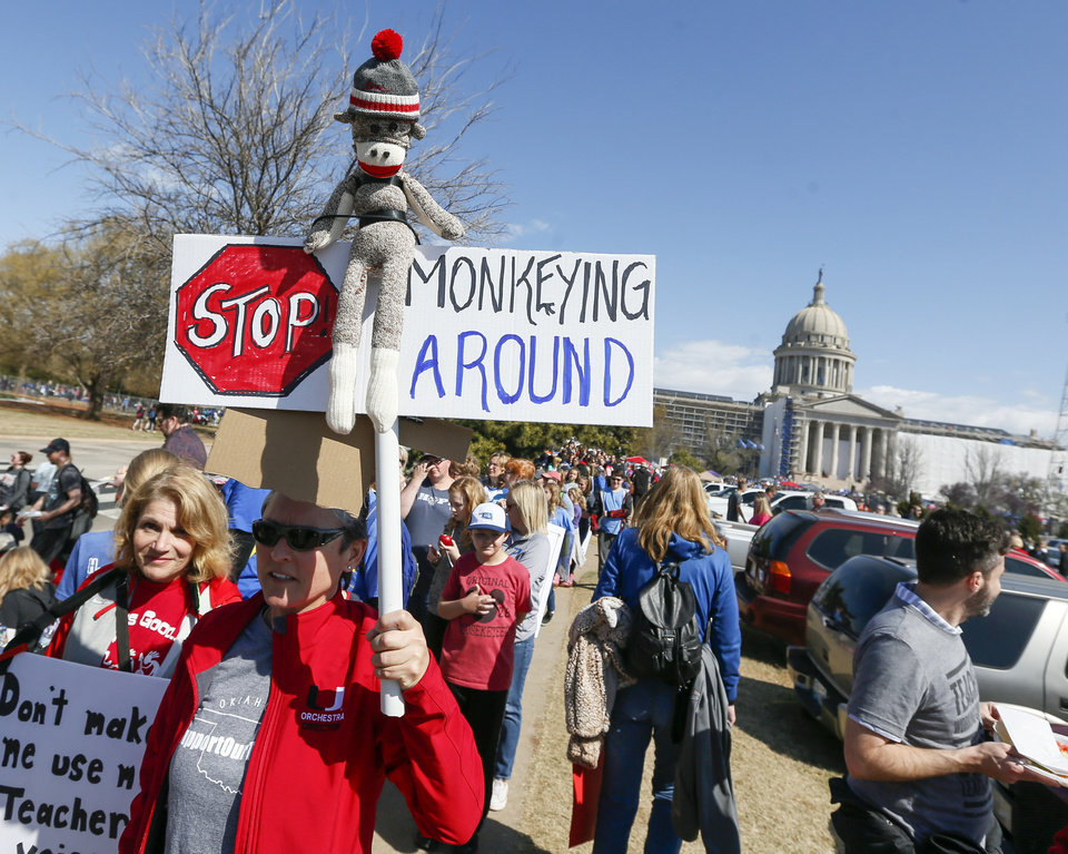 Photo - Paula Surface, holds a sign next to Janet Coleman as they wait in line for free tacos from Ted's Cafe Escondido during the eighth day of a walkout by Oklahoma teachers at the state Capitol in Oklahoma City, Monday, April 9, 2018. Surface and Coleman are orchestra teachers in Union Public Schools. Photo by Nate Billings, The Oklahoman