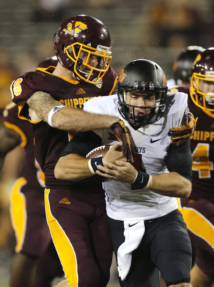 Photo - Oklahoma State's J.W. Walsh (4) is tackled by Central Michigan's Tony Annese (18) during the college football game between the Central Michigan Chippewas and the Oklahoma State University Cowboys at the Kelly-Shorts Stadium in Mount Pleasant, Mich., Thursday, Sept. 3, 2015. Photo by Sarah Phipps, The Oklahoman