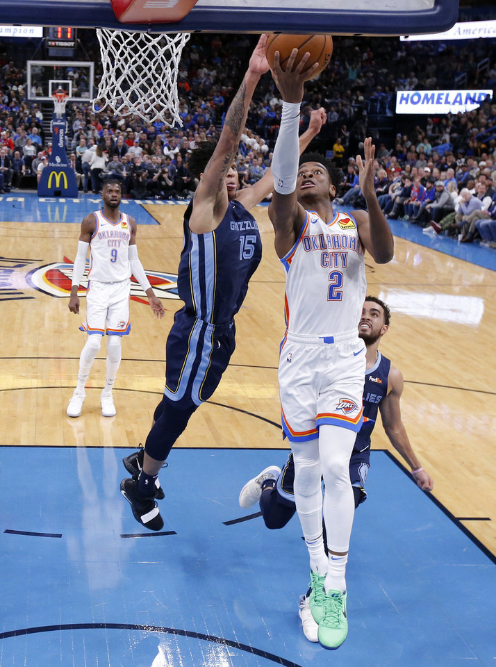 Photo - Oklahoma City's Shai Gilgeous-Alexander (2) goes past Memphis' Brandon Clarke (15) during an NBA basketball game between the Oklahoma City Thunder and the Memphis Grizzlies at Chesapeake Energy Arena in Oklahoma City, Wednesday, Dec. 18, 2019. Oklahoma City won 126-122. [Bryan Terry/The Oklahoman]