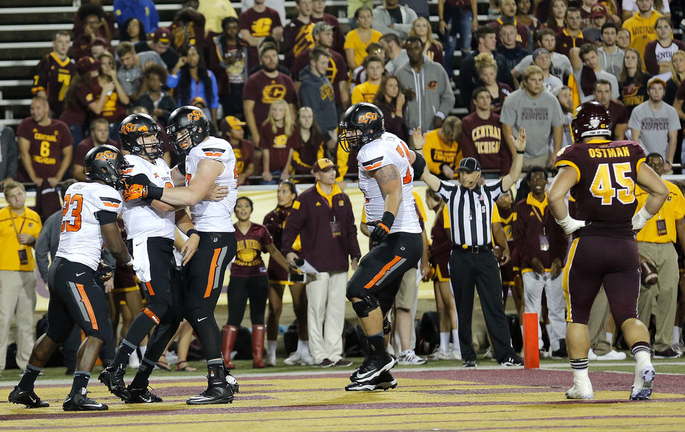 Photo - Oklahoma State celebrates a Oklahoma State's Mason Rudolph (2) touchdown as Central Michigan's Joe Ostman (45) walks of the field during the college football game between the Central Michigan Chippewas and the Oklahoma State University Cowboys at the Kelly-Shorts Stadium in Mount Pleasant, Mich., Thursday, Sept. 3, 2015. Photo by Sarah Phipps, The Oklahoman