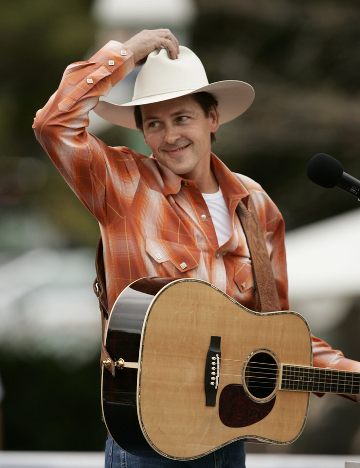 Photo - Singer Ty England acknowledges the crowd as he rides in the Oklahoma Centennial Parade on Sunday, Oct. 14, 2007, in Oklahoma City, Okla.  By STEVE SISNEY, The Oklahoman